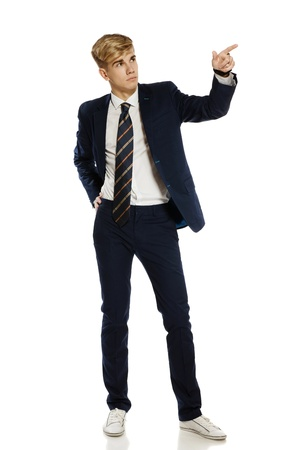 Full length portrait of a stylish young man pointing to the blank copy space, over white background photo
