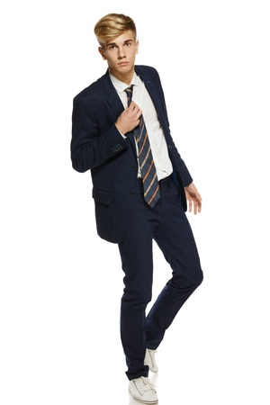 Full length portrait of a stylish young man in suit holding his tie, over white background Stock Photo - 16031769