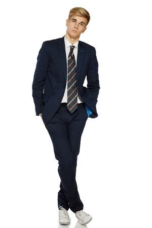 mani incrociate: Ritratto integrale di un uomo in piedi alla moda giovane in posa su sfondo bianco