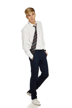 Full length portrait of a stylish young man in shirt and tie walking over white background