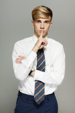Business man with finger on lips asking for silence over white background Stock Photo - 16032437