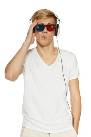 stereoscope: Disappointed man in three-dimensional glasses and headphones holding his head, over white background Stock Photo