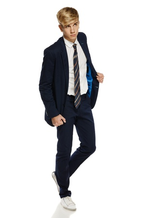 Full length portrait of a stylish young man walking over white background