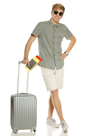 Full length of young male tourist standing with suitcase, holding tickets and passport, isolated on white background photo