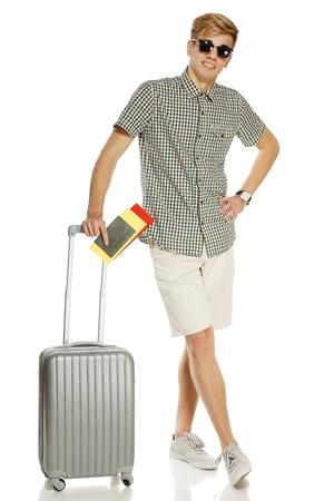 viajero: Longitud total de turista var�n joven de pie con la maleta, la celebraci�n de los billetes y pasaportes, aislados en fondo blanco
