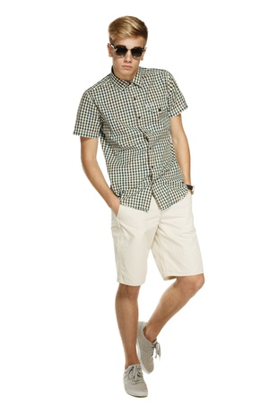 Young handsome male in shorts and sunglasses posing in full length with hands in pockets, over white background