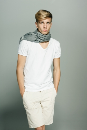 Young handsome male in shorts and scarf posing with hands in pockets photo