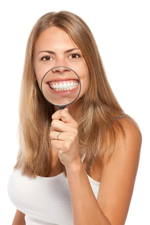 teeth whitening: Female with magnifying glass showing teeth over white background