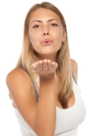 Cute young female blowing a kiss at you against white background photo