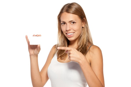 Woman pointing smiling at blank card sign with copy space over white background photo