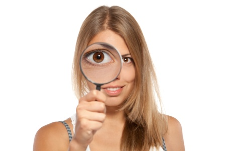 field glass: Close up of young female in casual looking through  the magnifying glass at you, with big magnified eye magnified, shallow deep of field, focus on the eye, over white background.