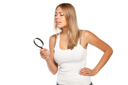 Side view of young smiling female looking through the loupe over white background photo