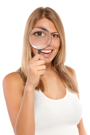 Closeup portrait of young smiling female looking through the loupe at you, isolated on white background Stock Photo - 16032343