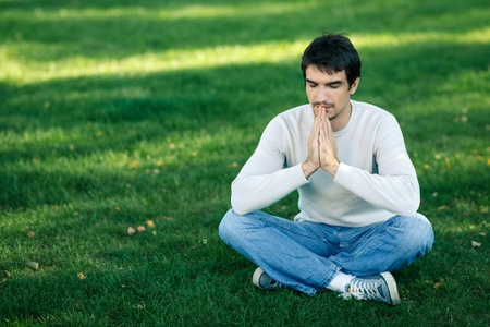 only adult: Young handsome male sitting in the lotus pose praying with hands pressed toghether