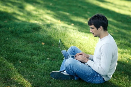 Young man with laptop outdoor sitting on the grass photo