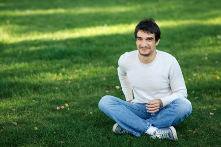 Young smiling male sitting on the grass outdoors photo