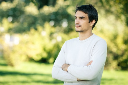 Young handsome man outdoors in fall clothing with autumn natural surroundings looking to the side, with copy space photo