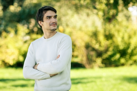 sideways: Young hansome smiling man outdoors looking to the side