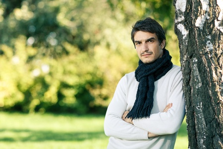 Young handsome man outdoors in fall clothing and scarf with autumn natural surroundings leaning on the tree stem, with copy space Stock Photo - 16032472