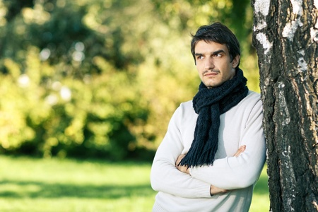 folded hands: Young handsome man outdoors in fall clothing and scarf with autumn natural surroundings leaning on the tree stem, looking to the side, with copy space Stock Photo