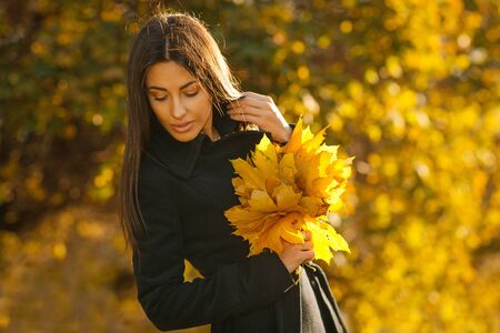 Autumn portrait of young woman in fall colors outdoors holding a bunch of yellow maple leaves Stock Photo - 16159306