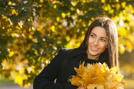 Autumn portrait of young woman in fall colors outdoors holding a bunch of yellow maple leaves looking to the side Stock Photo - 16159309