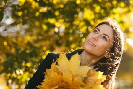 Autumn portrait of young woman in fall colors outdoors holding a bunch of yellow maple leaves photo