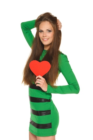 Young brunette lady in green dress posing with red heart shape on white background photo
