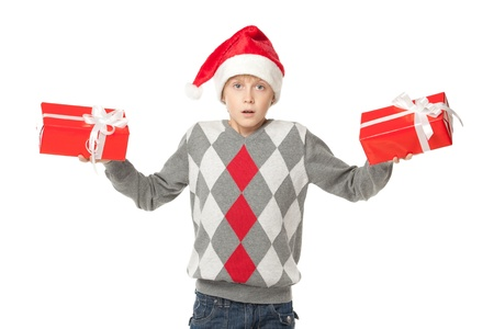 Confused boy in Santa hat holding two presents, over white background photo