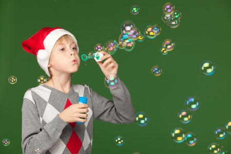 Boy in Santa hat blowing soap bubbles over green background photo