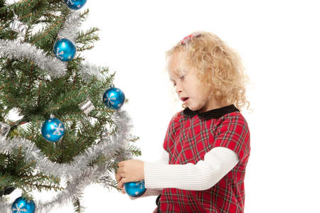 decorating christmas tree: Little girl decorating Christmas tree, over white background