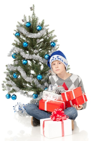 holding a christmas ornament: Pensive boy sitting near Christmas tree on the floor, holding presents, over white background