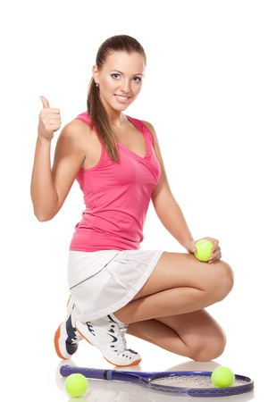 Full length of young tennis woman sitting in the squatting position and showing thumb up sign, on white background photo