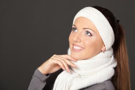 cintillos: Vista lateral de primer plano de una chica en ropa de abrigo mirando hacia arriba, sobre fondo gris