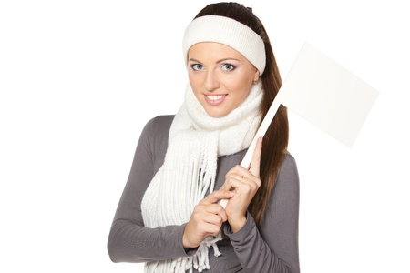 Woman in winter warm scarf and headband holding blank white flag   board sign  photo