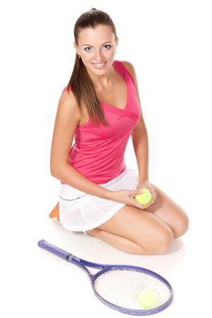 High angle view of young tennis female sitting on the floor with tennis ball in her hands, looking up photo