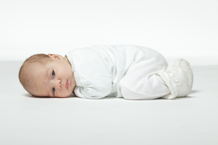 baby s: Newborn baby curled up lying on his stomach Stock Photo