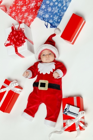 New born baby wearing Santa Claus costume suurounded by Xmas gifts, over white background photo