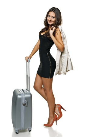 denim jacket: Full length of young woman with jacket over shoulder standing with silver suitcase, isolated on white background