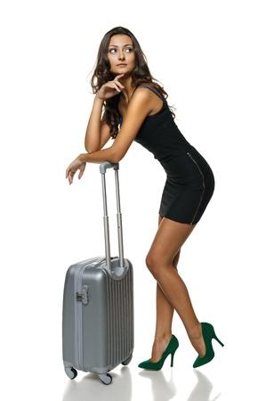 minifalda: Longitud total de joven mujer de pie apoyado en la maleta de plata mirando a la cara, aislado en fondo blanco