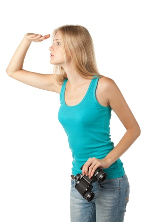 Side view of young blond woman looking forward, holding binoculars, isolated on white background
