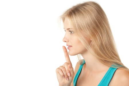 Side view of young woman with finger on lips over white background