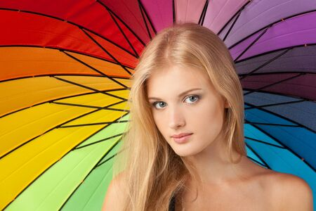 Close up portrait of beautiful blond female with rainbow umbrella background photo