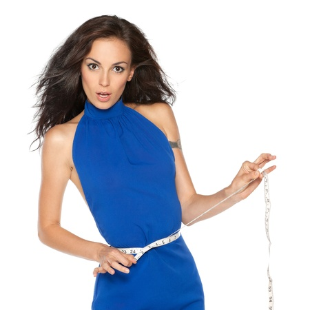 Pretty surprised woman in blue dress measuring waist with measurement type over white background photo