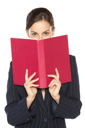 schoolmaster: Female in business suit peeking overthe book, isolated on white background Stock Photo