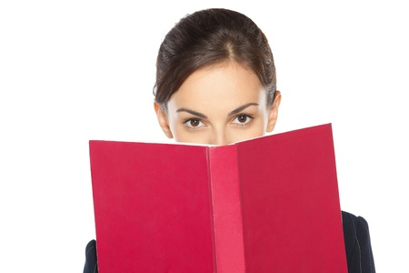 business attire teacher: Close-up portrait of female in business suit peeking over the book, isolated on white background