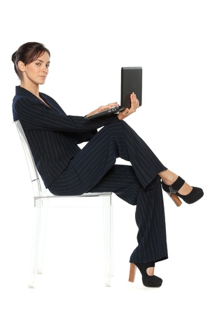 crossed legs: Full lenth portrait of a brunette businesswoman sitting in a transparent chair with laptop over white background, side view