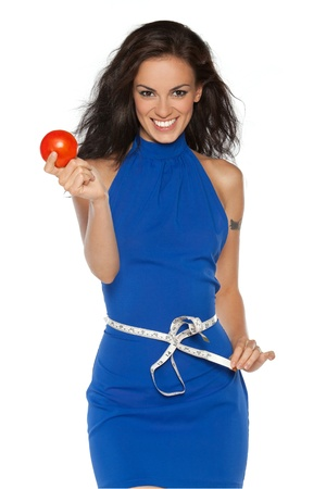 gain: Pretty smiling woman in blue dress measuring waist with measurement type, holding a tomato, isolated on white Stock Photo