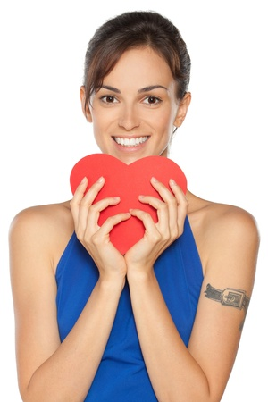 Young beautiful female in blue dress peeking from the heart shape isolated on white background photo