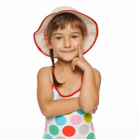 enfant maillot: Calme petite fille debout dans l'usure de natation et un chapeau panama, isol� sur fond blanc